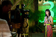 Female Brazilian TV television presenter, talking to camera with interesting lighting, cameraman in foreground. Reponte da Cancao music festival and song competition in Sao Lorenzo do Sul, RIo Grande do Sul, Brazil.
