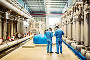 Two Japanese men in blue working in a water purification plant in Colorado
