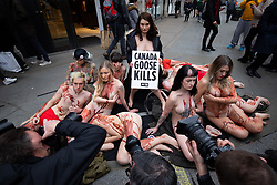 © Licensed to London News Pictures. 01/03/2019. London, UK. PETA (People for the Ethical Treatment of Animals) supporters demonstrate outside Canada Goose Regent Street store by covering themselves in fake blood and lying on coats similar to those made by Canada Goose. PETA want to put pressure on the clothing company, as PETA claim the fur used in their coats is sourced in a cruel manner. World Wildlife Day takes place on 3 March. Photo credit : Tom Nicholson/LNP