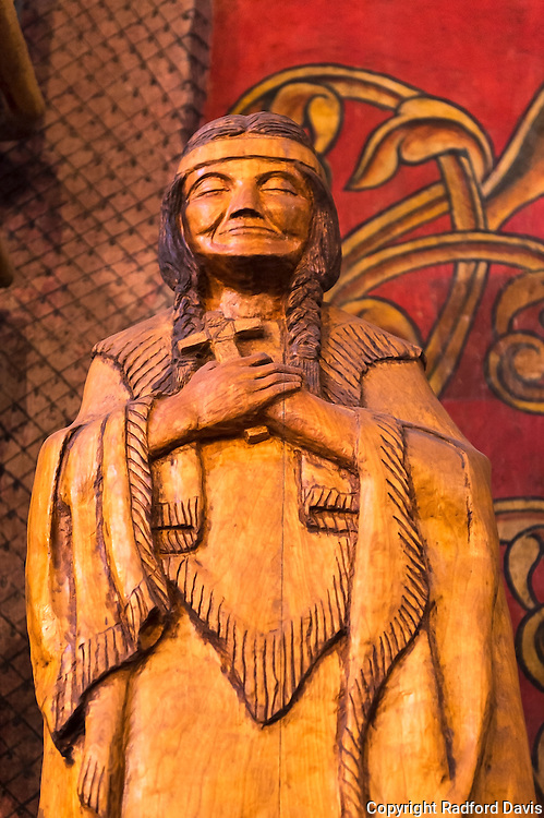 A statue of native watches over worshippers.
