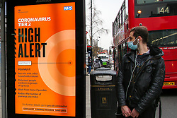 © Licensed to London News Pictures. 10/12/2020. London, UK. A man wearing face covering looks at 'Coronavirus Tier 2 High Alert' public information campaign digital poster in north London amid fears of London going into tougher lockdown restrictions as early as next week. According to Public Health England, 24 of the London's 32 boroughs recored a rise in infections one week after second lockdown. Photo credit: Dinendra Haria/LNP