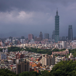 The Taipei 101, with one of Taiwans biggest cemetery to the right<br /> <br /> Formerly known as the Taipei World Financial Center - the super tall skyscraper was officially classified as the world's tallest from its opening in 2004 until the 2010 completion of the Burj Khalifa in Dubai, United Arab Emirates.<br /> <br /> Taipei 101's postmodernist architectural style evokes Asian traditions in a modern structure employing industrial materials. Its design incorporates a number of features that enable the structure to withstand the Pacific Rim's earthquakes and the region's tropical storms.