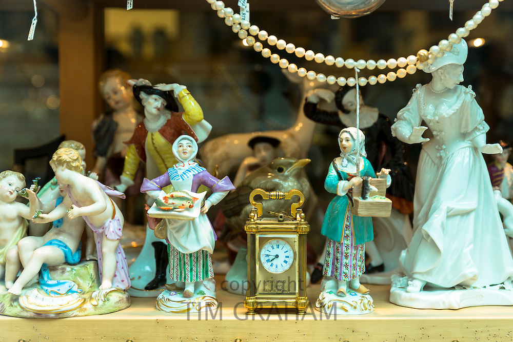Porcelain figures and clock on display at Bordhin antique shop in Burgstrasse in Munich, Bavaria, Germany