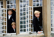 Eton schoolboys in traditional tails looking through the window at Eton College, England, UK