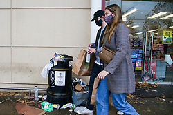 © Licensed to London News Pictures. 08/11/2020. London, UK. Women wearing face coverings walk past an overflowing bin. Restaurants are currently only providing take away services due to the second coronavirus lockdown, which is resulting in bins overflowing outside shops in Haringey Arena Shopping Park, north London. The lockdown will last until Wednesday 2 December, to control the increase of coronavirus cases. Photo credit: Dinendra Haria/LNP
