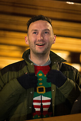 © Licensed to London News Pictures . Manchester , UK . A man wearing a Christmas jumper . FILE PHOTO DATED 20/11/2013 of Christmas Markets in Manchester as temperatures drop and 2014 seasonal markets start up across the country , selling mulled wine , german hot dogs , dutch pancakes , wooly hats and many other festive frivolities . Christmas markets provide an economic boost to many city centres and create a festive atmosphere on otherwise cold and dark nights . . Photo credit : Joel Goodman/LNP