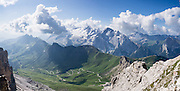 A lift from Passo Pordoi up to Sass Pordoi in the Sella Group gives a sweeping view of Dolomites peaks including their highest, glacier-clad Marmolada (3343 meters / 10,968 feet), Italy. From Pordoi Pass on state highway 48 (Grand Strader delle Dolomiti), take the rapid cable car ascent or hike up to the restaurant on Sass Pordoi at 2952m. Pordoi Pass (or Pordoijoch, 2239 meters/7346 feet) is the highest surfaced road traversing a pass in the Dolomites. On the Padon chain in the foreground (a ridge of volcanic origin carpeted with lush green pasture and wildflowers), we highly recommend hiking the Bindelweg/Viel del Pan trail starting from Pordoi Pass. The Dolomites are part of the Southern Limestone Alps, Europe. UNESCO honored the Dolomites as a natural World Heritage Site in 2009. This panorama was stitched from 2 overlapping photos.