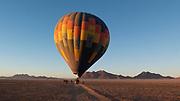 A hot air balloon at sunrise take off in the Namib-Naukluft National Park, Namibia.