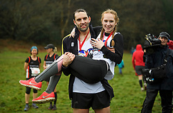 © Licensed to London News Pictures. 03/03/2019. Dorking, UK. Winners of the race CHRIS HEPWORTH and TANISHA PRINCE pose for a picture after Chris Hepworth proposed to Tanisha Prince at the finish line. Competitors take part in the 2019 annual Wife Carrying Race in Dorking, Surrey. Run over a course of 380m, with both men and women carry a 'wife' over obstacles, the race is believed to have originated in the UK over twelve centuries ago when Viking raiders rampaged into the northeast coast of England carrying off any unwilling local women . Photo credit: Ben Cawthra/LNP