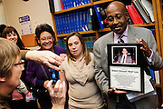 """Cook County Public Defender Judge Abishi C. Cunningham Jr. (right to left) displays a plaque honoring the late Public Defender Robert Emmett Lee following a dedication ceremony attended by Lee's daughter Moriah A. Lee, wife Debra J. Lee and daughter Morgan M. Munro at the Cook County Criminal Courts Administration Building Wednesday, December 12th, 2012. The beloved Lee joined the office in 1973, """"serving the poor with ferocity and passion"""" as included in a tribute from the Department newsletter The Credo. Lee died suddenly last May. © 2012 Brian J. Morowczynski ViaPhotos"""