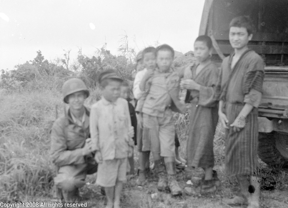 American GI poses for a photo with Japanese children on Okinawa in a circa 1945 photograph after the U.S. invasion.