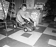 Electric Car Race at Supermarkets.<br /> 1971.<br /> 30.10.1971.<br /> 10.30.1971.<br /> 30th October 1971.<br /> Elect car races were held in Powers Supermarkets in Stillorgan,Blackrock Co Dublin and in Bray Co Wicklow.<br /> <br /> Image shows this young man as he sets off in the electric car for his circuit of the store.