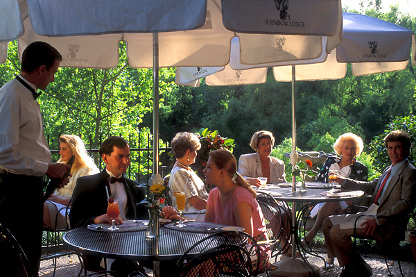 Stock photo of groups dining under umbrellas on an outdoor patio