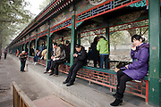 Visitors sit along the Long Corridor (Chang Lang) at The Summer Palace, Beijing, China