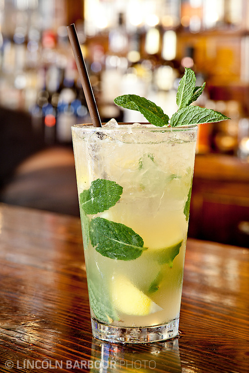 A pristine looking Mojito in a pint glass stands on a wooden bar. Many other bottles of alcohol are out of focus in the background.