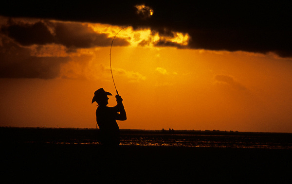 Stock photo of the silhouette of a man reeling in a fish at sunset