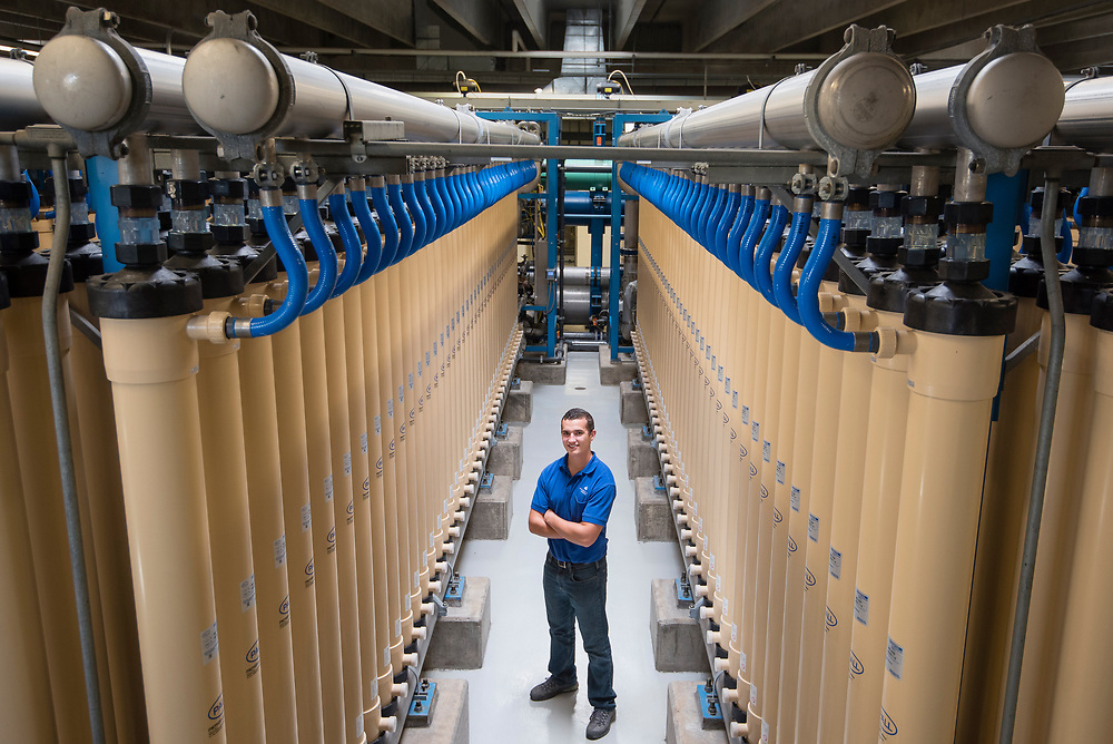 Portrait of a man in a water treatment plant standing between the water filters.