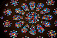 Medieval western rose  window of the Gothic Cathedral of Chartres, France. A UNESCO World Heritage Site. The western rose, made c.1215 and 12m in diameter shows the Last Judgement - a traditional theme for west façades. A central oculus showing Christ as the Judge is surrounded by an inner ring of 12 paired roundels containing angels and the Elders of the Apocalypse and an outer ring of 12 roundels showing the dead emerging from their tombs and the angels blowing trumpets to summon them to judgement.