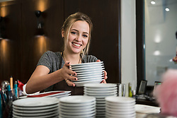 Smiling woman arranging stack of clean plates at restaurant