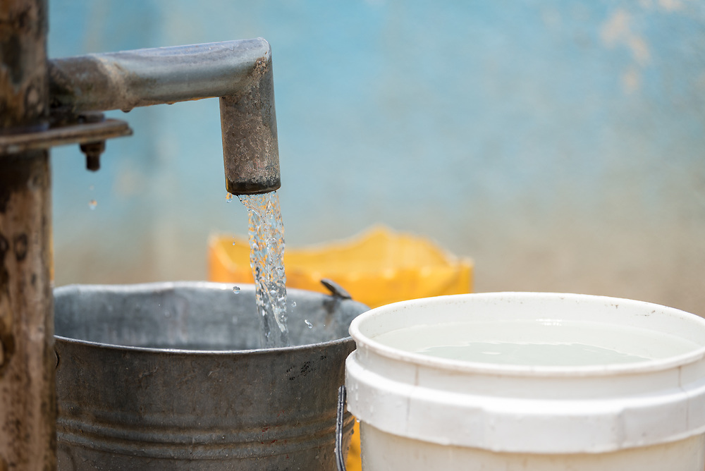 30 May 2019, Mokolo, Cameroon: Water is pumped into a metal bucket at one of the boreholes through which the Lutheran World Federation's World Service programme supplies drinking water to refugees in Minawao. The Minawao camp for Nigerian refugees, located in the Far North region of Cameroon, hosts some 58,000 refugees from North East Nigeria. The refugees are supported by the Lutheran World Federation, together with a range of partners.