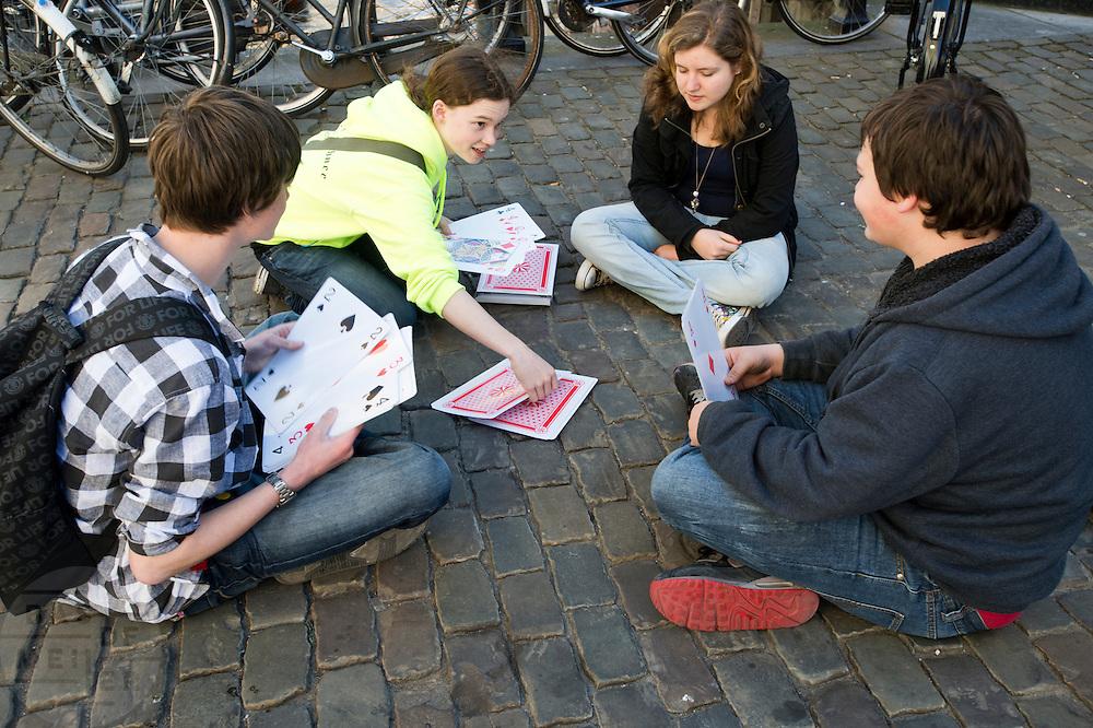 Jongeren kaarten op de Stadhuisbrug in Utrecht.<br /> <br /> Young people are playing cards in Utrecht.