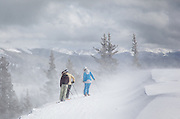 Skiers contemplate a steep slope as a fierce wind blows fresh powder on the last day of the ski season at Monarch Mountain.