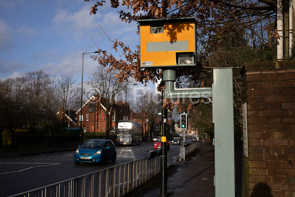 Cars passing a yellow speed camera in Wake Green on 16th Febuary 2020 in Birmingham, United Kingdom.  A traffic enforcement camera is a camera which may be mounted beside or over a road or installed in an enforcement vehicle to detect traffic regulation violations, including speeding.