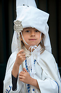 A young member of La Resurreccion poses for a portrait in a break of the long walk towards the Cathedral of Seville on Easter Day. Andalusia, Spain