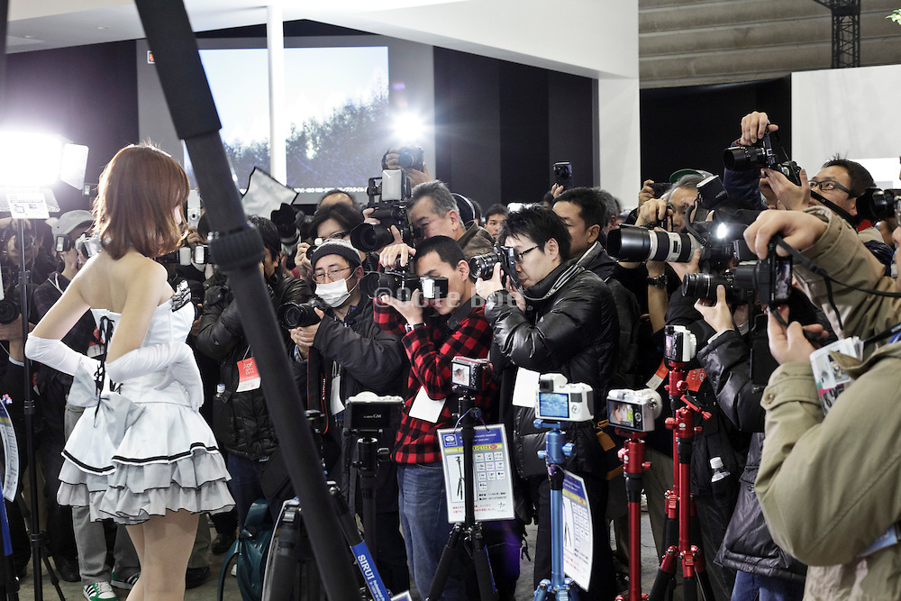 model being photographed by amateur photographers at the Camera & Photo Imaging trade show in Yokohama