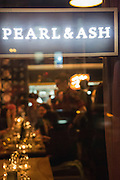 The dining room of Pearl & Ash seen from the street at night.