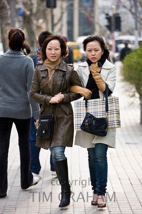 Women walking arm in arm on Nanjing Road, central Shanghai, China