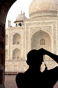 Silouhette of photographer taking picture of the Taj Mahal, a UNESCO World Heritage Site, at Agra, India
