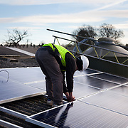 Jake Beautyman installs solar panels on a barn roof on Grange farm, near Balcombe. The installation is part of an initiative by local residents in Balcombe to encourage more people to use renewable energy rather than energy based on carbon such as fracking. The initaitive is called Repowerbalcombe and is supported by the charity 10:10.