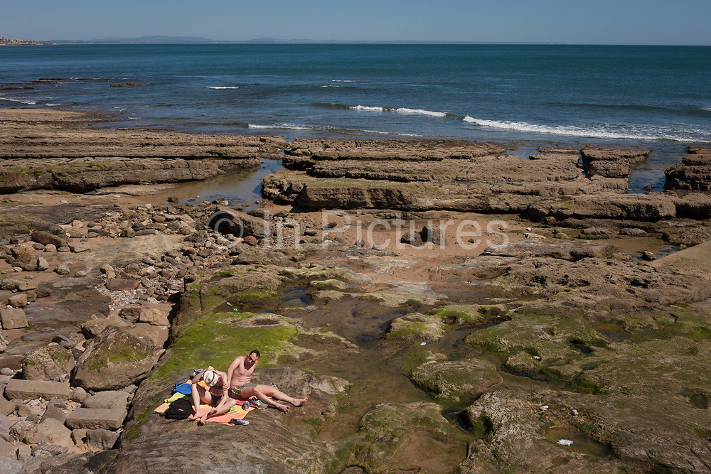 A man and woman sit on rocks rubbing in sunblock with Atlantic waves coming in the background, on 12th July 2016, at Estoril, near Lisbon, Portugal. Cascais is a coastal town and a municipality in Portugal, 30 kilometres 19 miles west of Lisbon. The former fishing village gained fame as a resort for Portugals royal family in the late 19th century and early 20th century. Nowadays, it is a popular vacation spot for both Portuguese and foreign tourists and located on the Estoril Coast also known as the Portuguese Riviera.