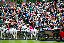 © London News Pictures. 18/06/2013. Ascot, UK.  Crowds watch and take pictures as HRH Queen Elizabeth II arrives in a carriage for day one of Royal Ascot at Ascot racecourse in Berkshire, on June 18, 2013.  The 5 day showcase event,  which is one of the highlights of the racing calendar, has been held at the famous Berkshire course since 1711 and tradition is a hallmark of the meeting. Top hats and tails remain compulsory in parts of the course. Photo credit should read: Ben Cawthra/LNP