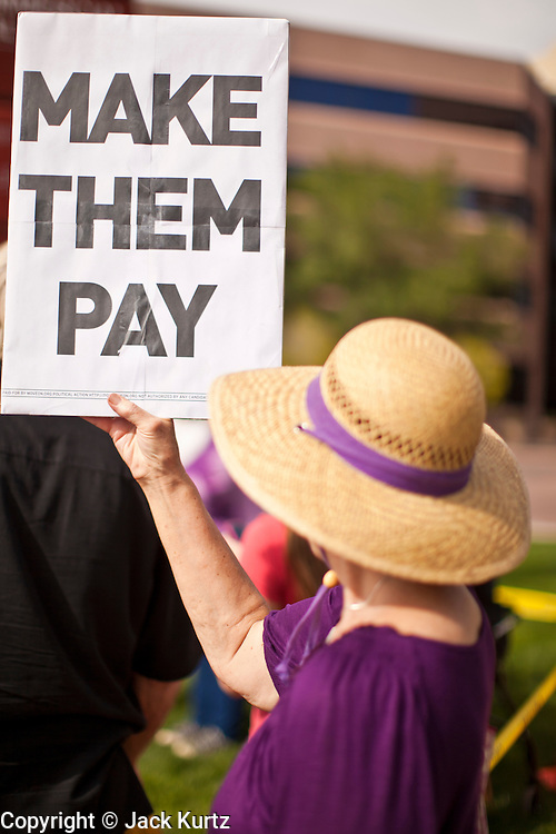 18 APRIL 2011 - PHOENIX, AZ: A member of MoveOn.org pickets the office of Sen. John McCain Monday. About 50 members of MoveOn.org gathered at the office of US Sen. John McCain (R-AZ) in Phoenix, AZ, Monday, Apr. 18, to draw attention to corporations that don't pay U.S. taxes. A representative of the group went into McCain's office present the Senator's staff with a tax bill for the 12 corporations they say paid no US income taxes.      Photo by Jack Kurtz