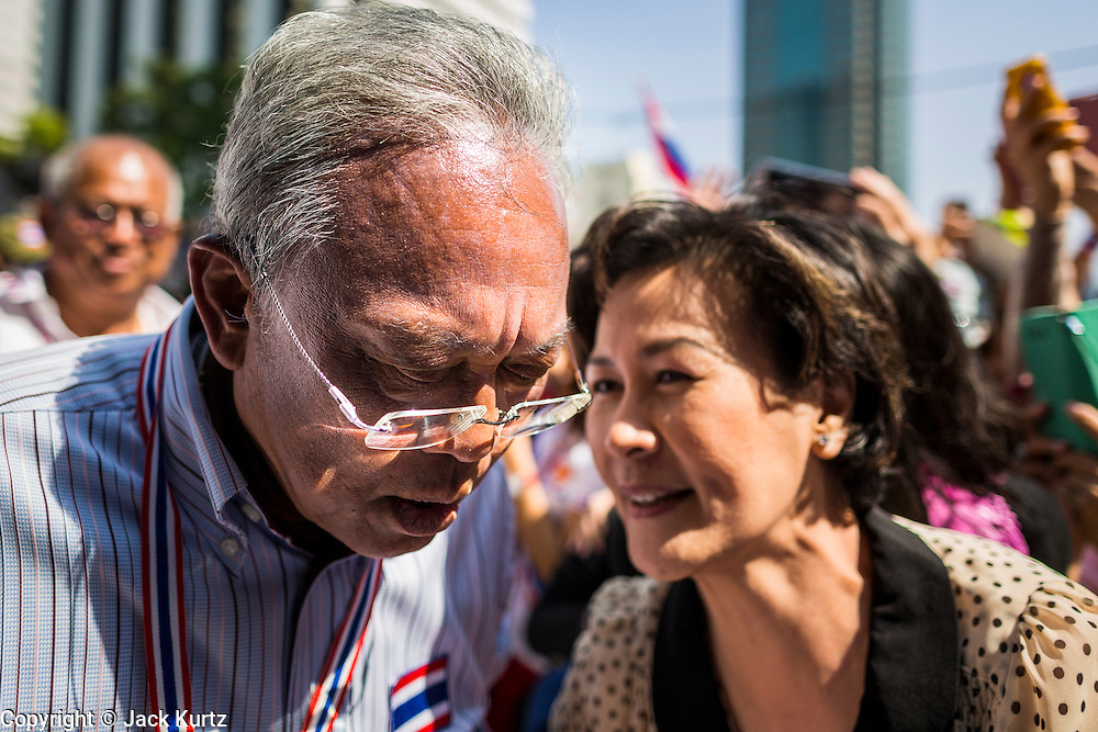 21 JANUARY 2014 - BANGKOK, THAILAND:  SUTHEP THAUGSUBAN, talks to a supporter during a march down Thanon Naradhiwas Rajanagarindra in the financial district of Bangkok. Suthep, the leader of the anti-government protests and the People's Democratic Reform Committee (PDRC), the umbrella organization of the protests, led a march through the financial district of Bangkok Tuesday. Shutdown Bangkok has entered its second week with no resolution in sight. Suthep is still demanding the caretaker government of Prime Minister Yingluck Shinawatra resign and the PM says she won't resign and intends to go ahead with the election.    PHOTO BY JACK KURTZ