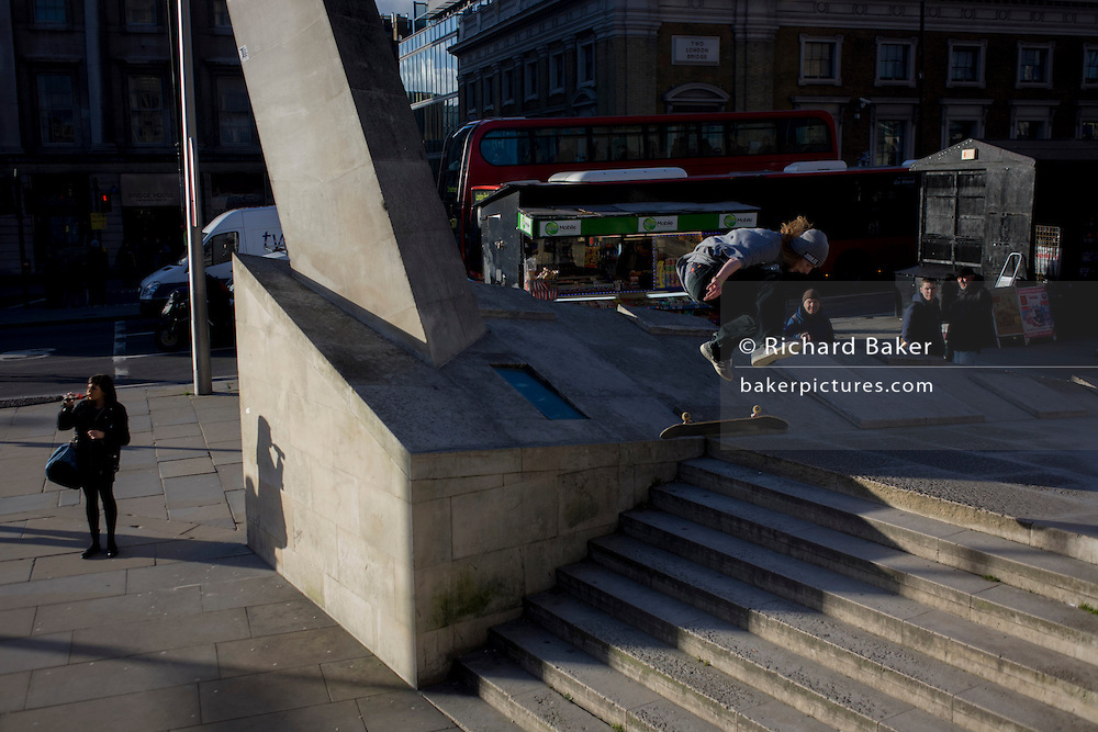 A young woman drinks, unaware of a young skateboarder flying through the air during his acrobatic jump over steps during London's rush hour.