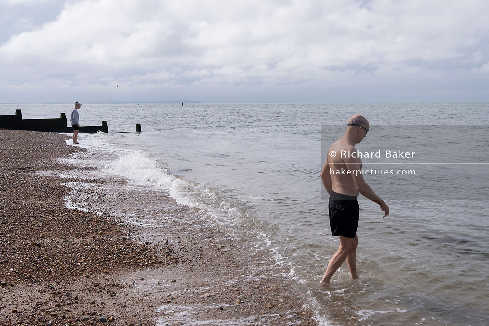 A sea swimmer enters the tidal waters of the Thames Estuary, on 25th July 2021, in Whitstable, England.
