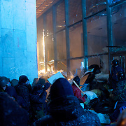 January 26, 2014 - Kiev, Ukraine: Ukrainian protesters laid siege to Ukrainian House international convention center, a Soviet-era building in central Kiev, used as a base by the security forces, who remained holed up inside.Some two thousand stick-wielding protesters clad in helmets threw Molotov cocktails and smashed in windows of the Ukrainian House, climbing over sandbags into the building. The security forces protected themselves with riot shields as well as by hurling stun grenades and attempting to douse the protesters with jets of water.The protesters later in the night formed a corridor on the steps of the building to allow the security forces to leave. (Paulo Nunes dos Santos)