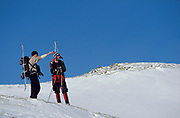 Cross Country Walker Skiers looking at view of snowy landscape, hiking, white, blue sky, remote
