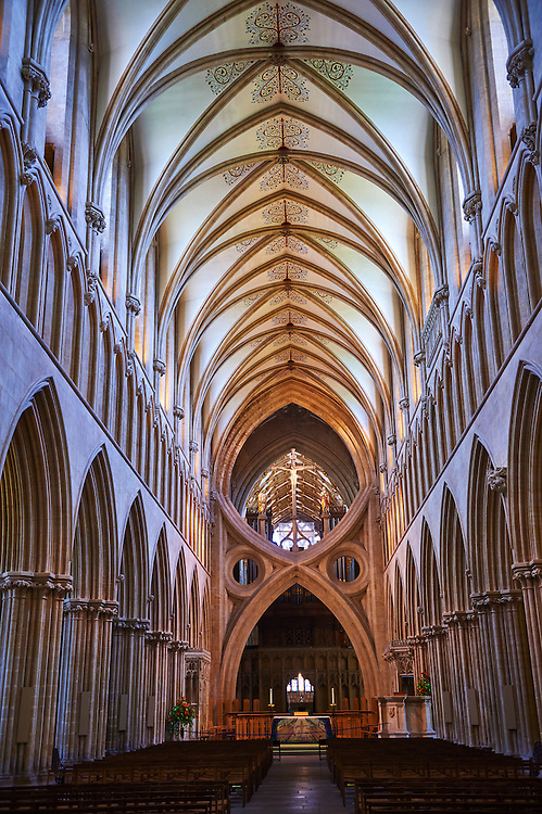 """The aisle of the medieval Wells Cathedral built in the Early English Gothic style in 1175, Wells Somerset, England . Its Gothic architecture is mostly in Early English style of the late 12th – early 13th centuries. Building began about 1175 at the east end with the choir. Historian John Harvey sees it as Europe's first truly Gothic structure. Its Early English front with 300 sculpted figures, is seen as a """"supreme triumph of the combined plastic arts in England"""".<br /> <br /> Visit our MEDIEVAL PHOTO COLLECTIONS for more   photos  to download or buy as prints https://funkystock.photoshelter.com/gallery-collection/Medieval-Middle-Ages-Historic-Places-Arcaeological-Sites-Pictures-Images-of/C0000B5ZA54_WD0s"""
