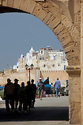 Fishermen head through an old gate towards the dock from the medina of Essaouira in Morocco