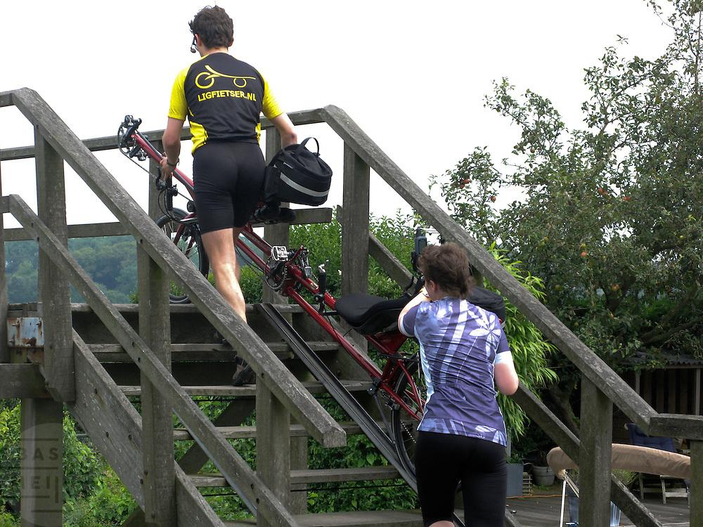 Jos en Hankie sjouwen de ligtandem een bruggetje over op de route.<br /> <br /> Two people are carrying their recumbent tandem over a bridge.
