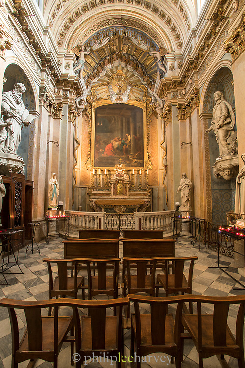 Interior of Grasse Cathedral benches facing altar with painting, host, statues and candles, Notre-Dame-du-Puy de Grasse, Grasse, France