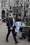 A City man carries a bunch of inflated balloons through Cornhill in the City of London, the capitals financial district, on 14th March 2018, in London England.