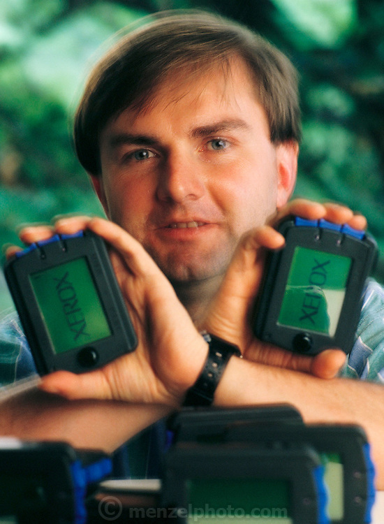"Roy Want holds his invention - the Xerox parctab. This hand-held, 200-gram prototype allows the user to beam information to a personal computer by writing a series of shorthand-like symbols, each of which represents a letter of the alphabet, on a pressure-sensitive screen. Want is a researcher at Xerox PARC (Palo Alto Research Centre) in California's Silicon Valley. One of the most innovative computer companies in the USA, PARC is the birthplace of the mouse, the computer workstation and the ""graphical user interface"", the now-universal system of windows and icons that makes it possible for a novice to use a computer. (1995)"