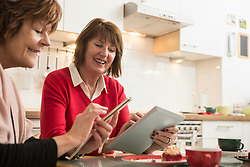 Two senior women using smart phone and digital tablet in kitchen, Munich, Bavaria, Germany