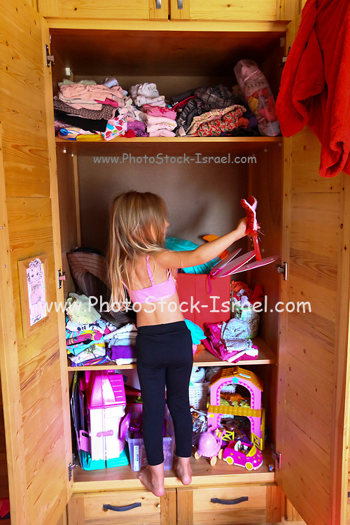 Young girl of four chooses clothes from a messy closet