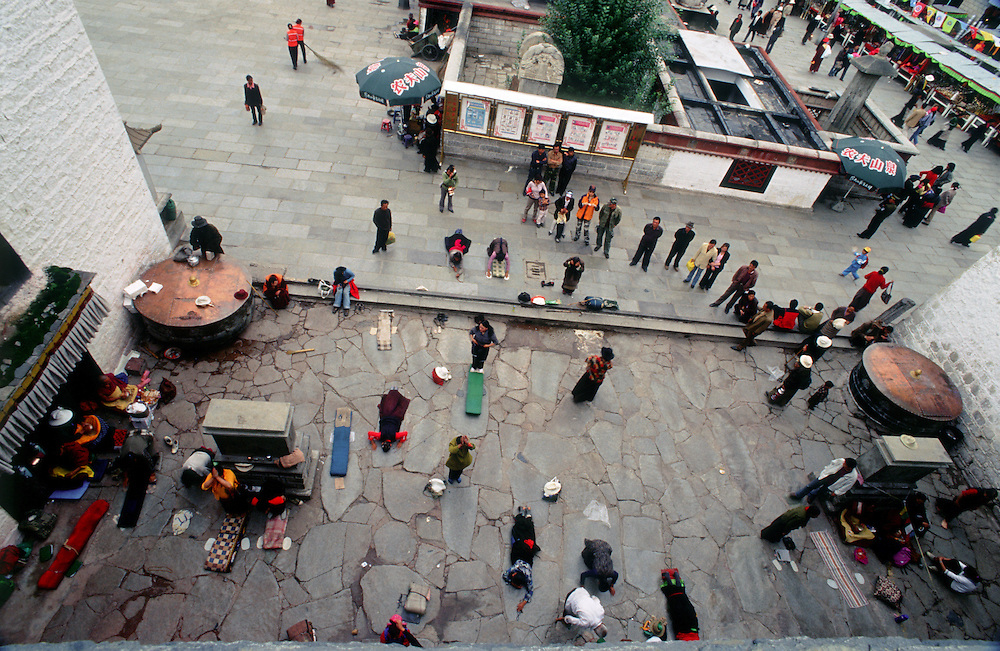 Lhasa, Tibet, pilgrims prostrating outside the Jokhang Temple, the most sacred site in Tibetan Buddhism.